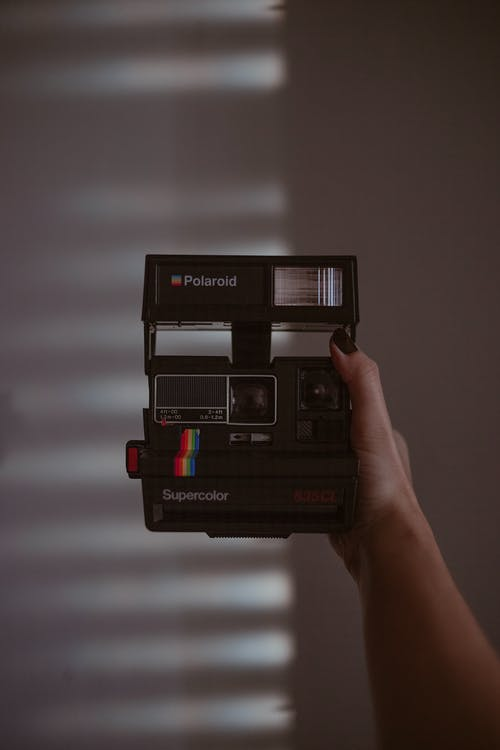 Person Holding Black Polaroid Instant Camera