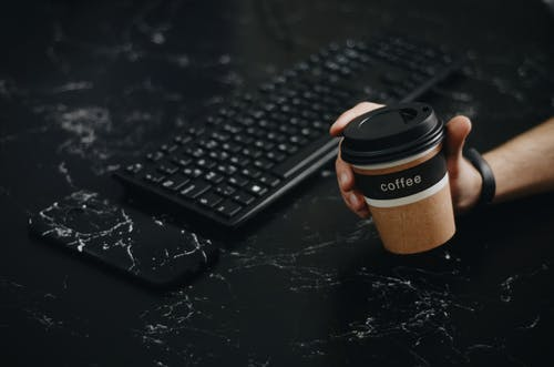 Person Holding Brown Disposable Cup Near Wireless Keyboard