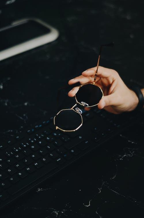 Безкоштовне стокове фото на тему «клавіатура, окуляри, Рука, сонцезахисні окуляри»
