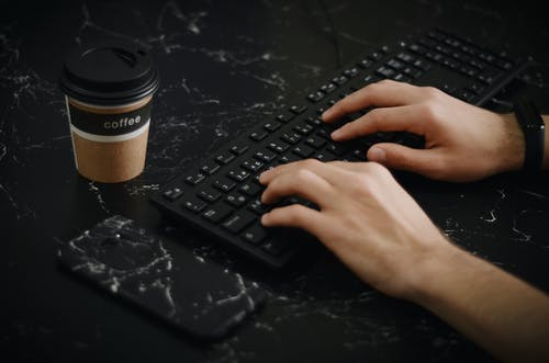 Person Using Keyboard Beside Phone and Coffee Cup