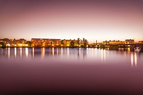 Brown Lighted Buildings Near the Body of Water Landscape Photo