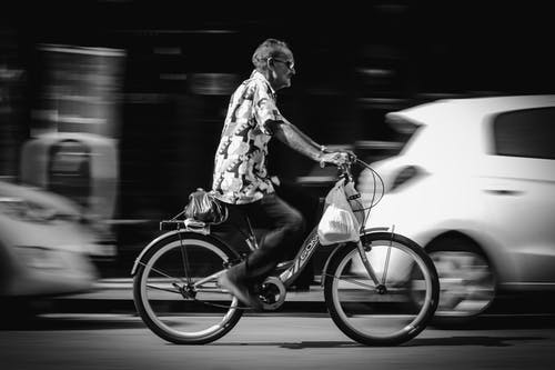 Greyscale Photo of Man Riding Bicycle on Road Passing Vehicles