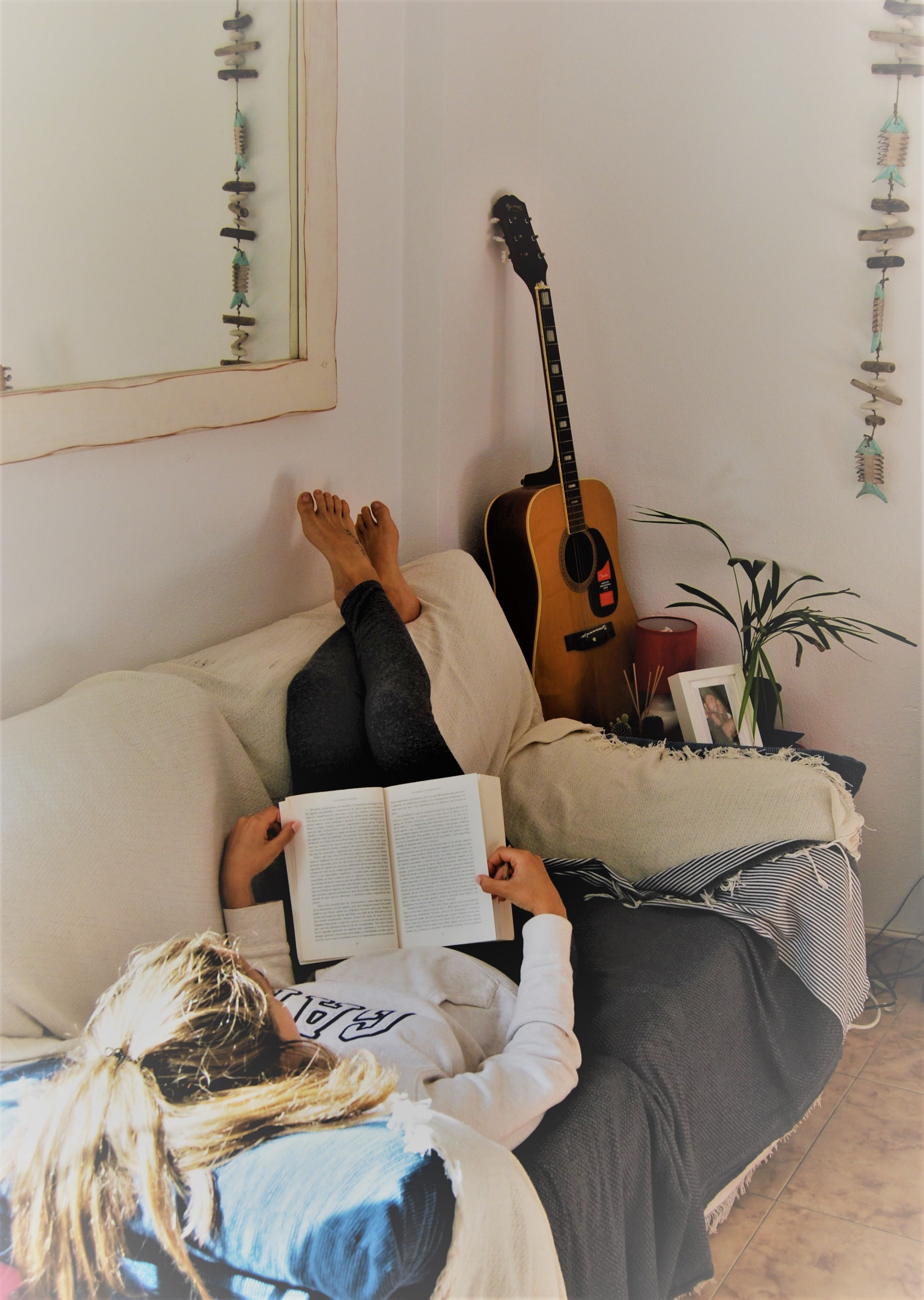 Woman Reading Book While Lying On Sofa