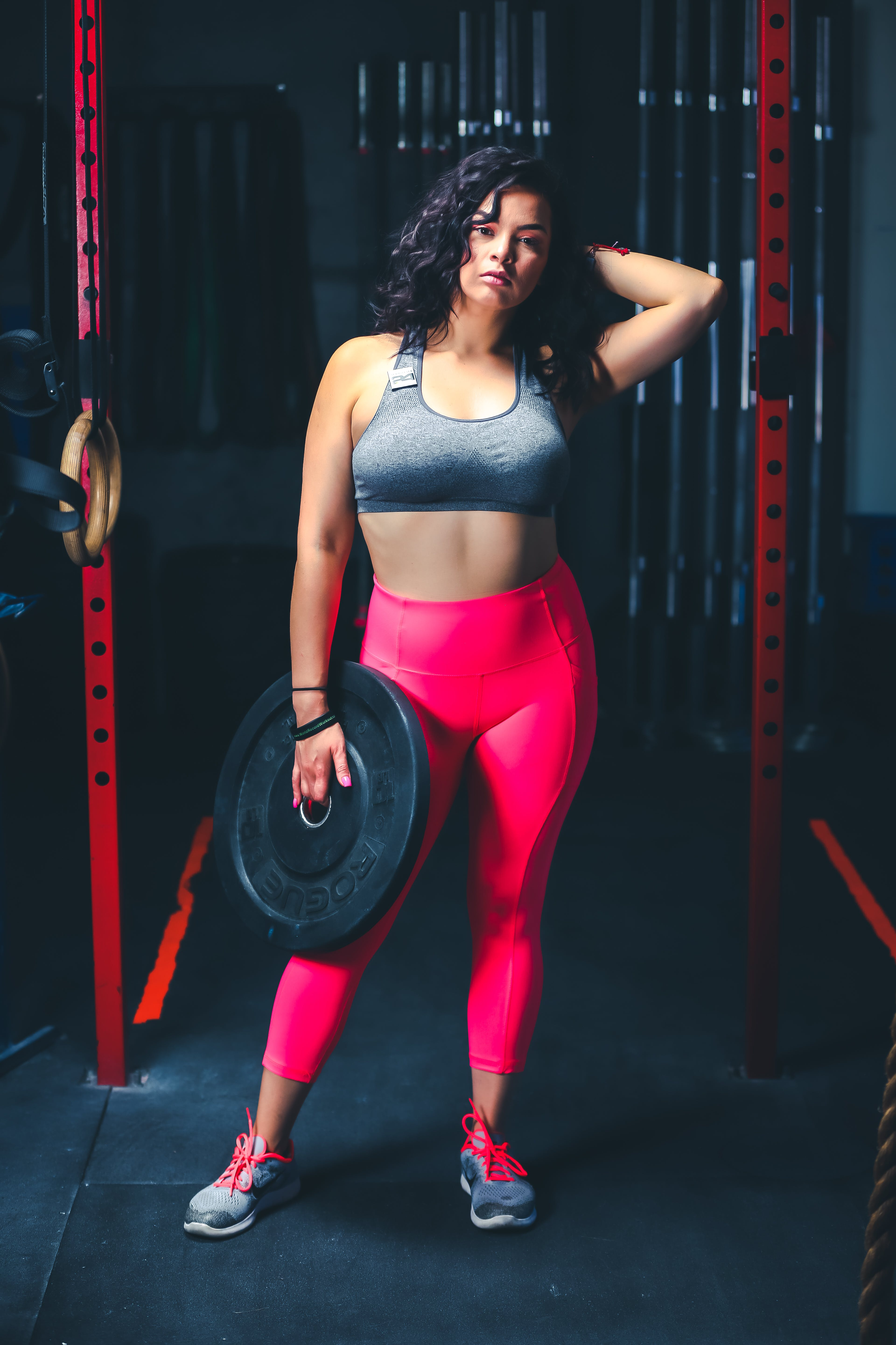 Woman In Grey Sports Bra And Pink Leggings Holding Black Weight Plate
