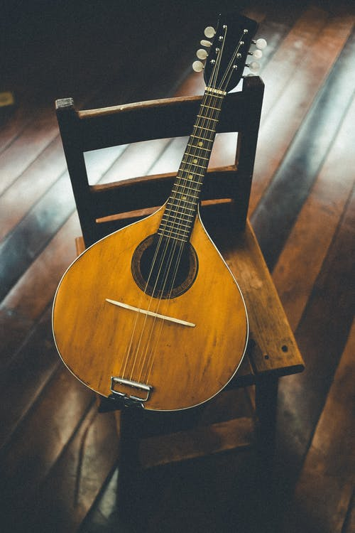 Brown Mandolin String Instrument on Brown Wooden Chiar