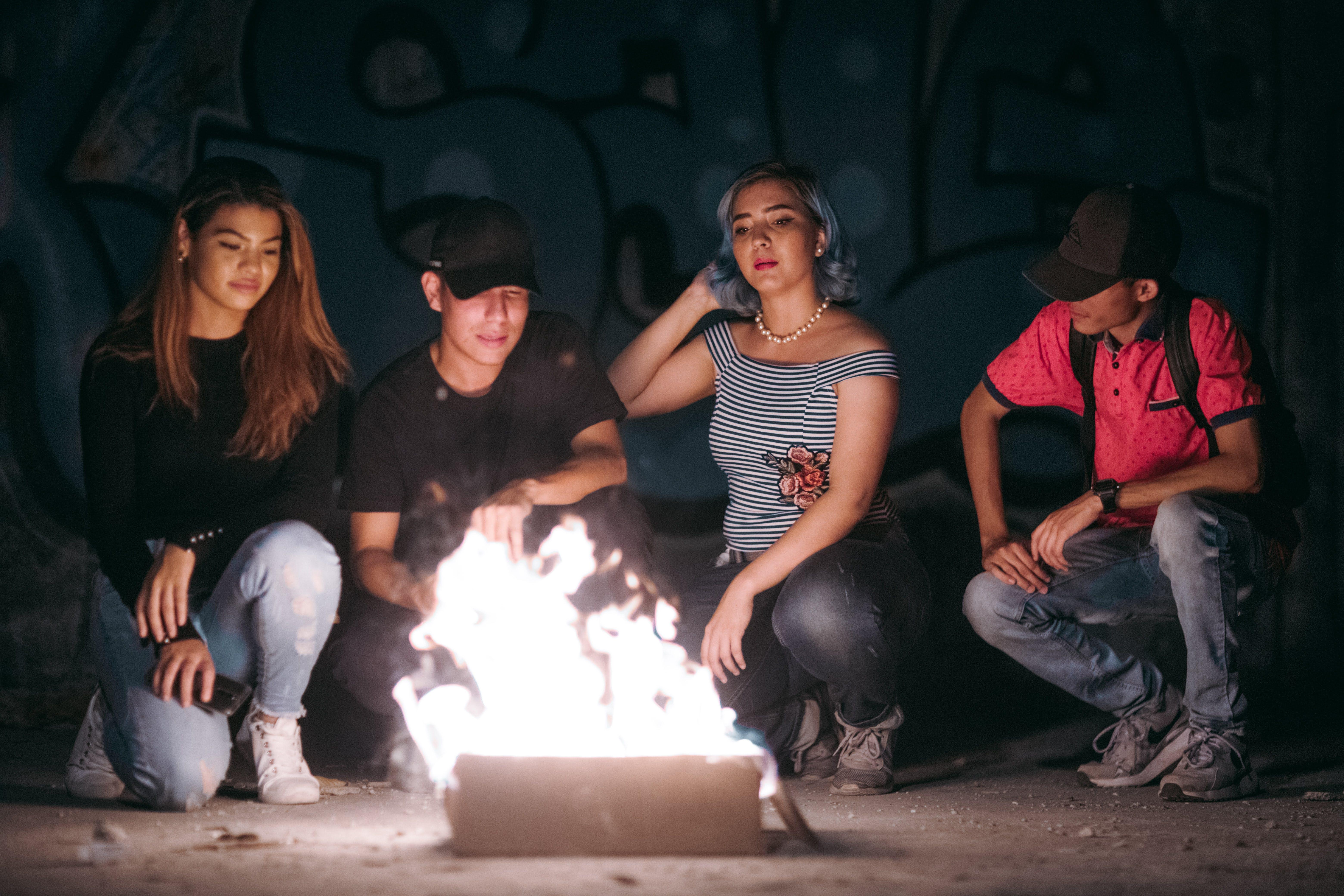 Two Men And Women Sitting Near Burning Box