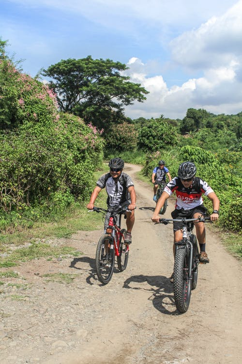 3 Men Riding Bicycles on Dirt Road