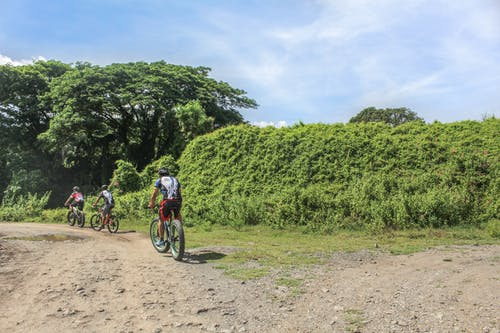 People Riding Bicycles on Dirt Road