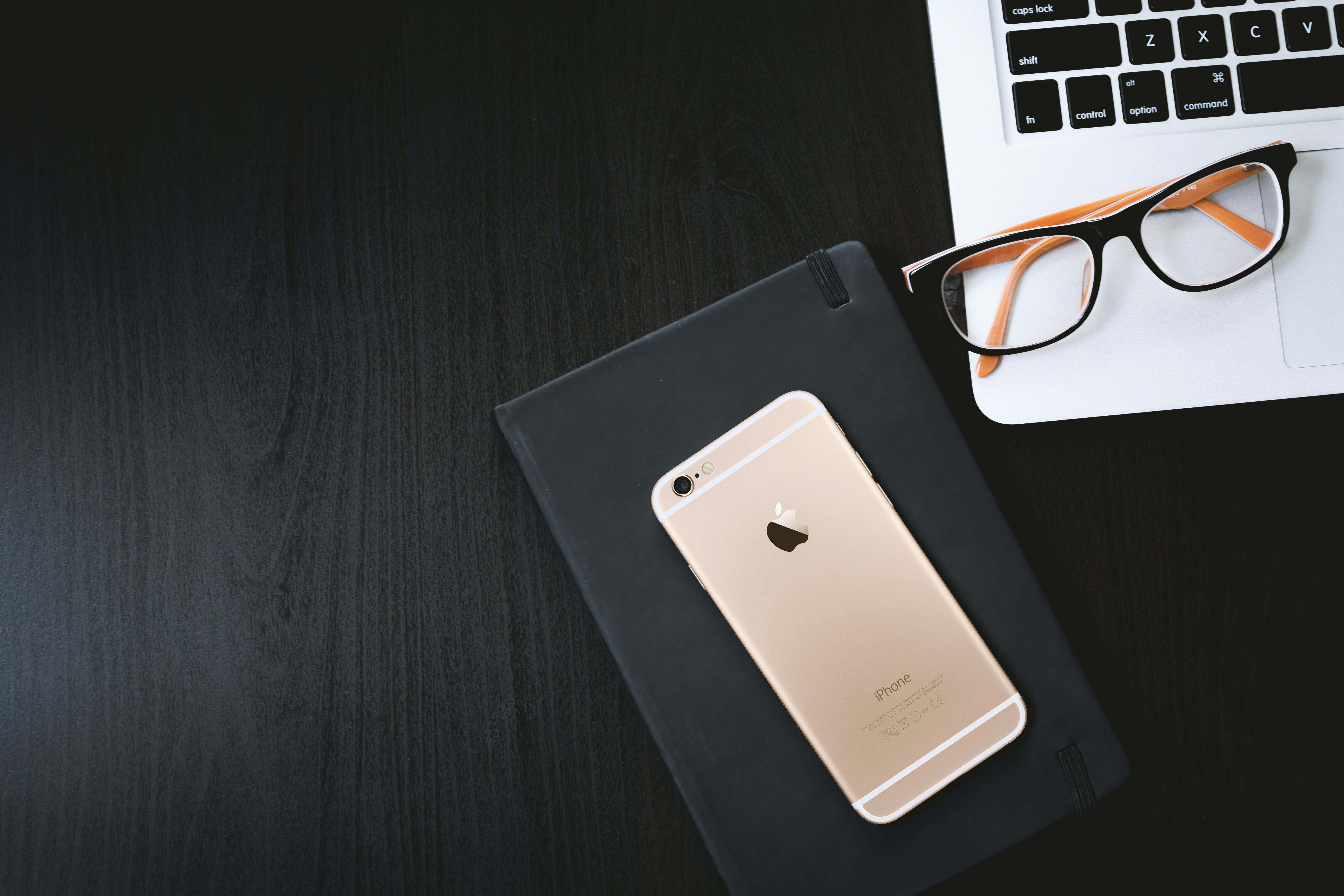 Gold Iphone 6 on Black Case Besides Eyeglasses on Silver Macbook