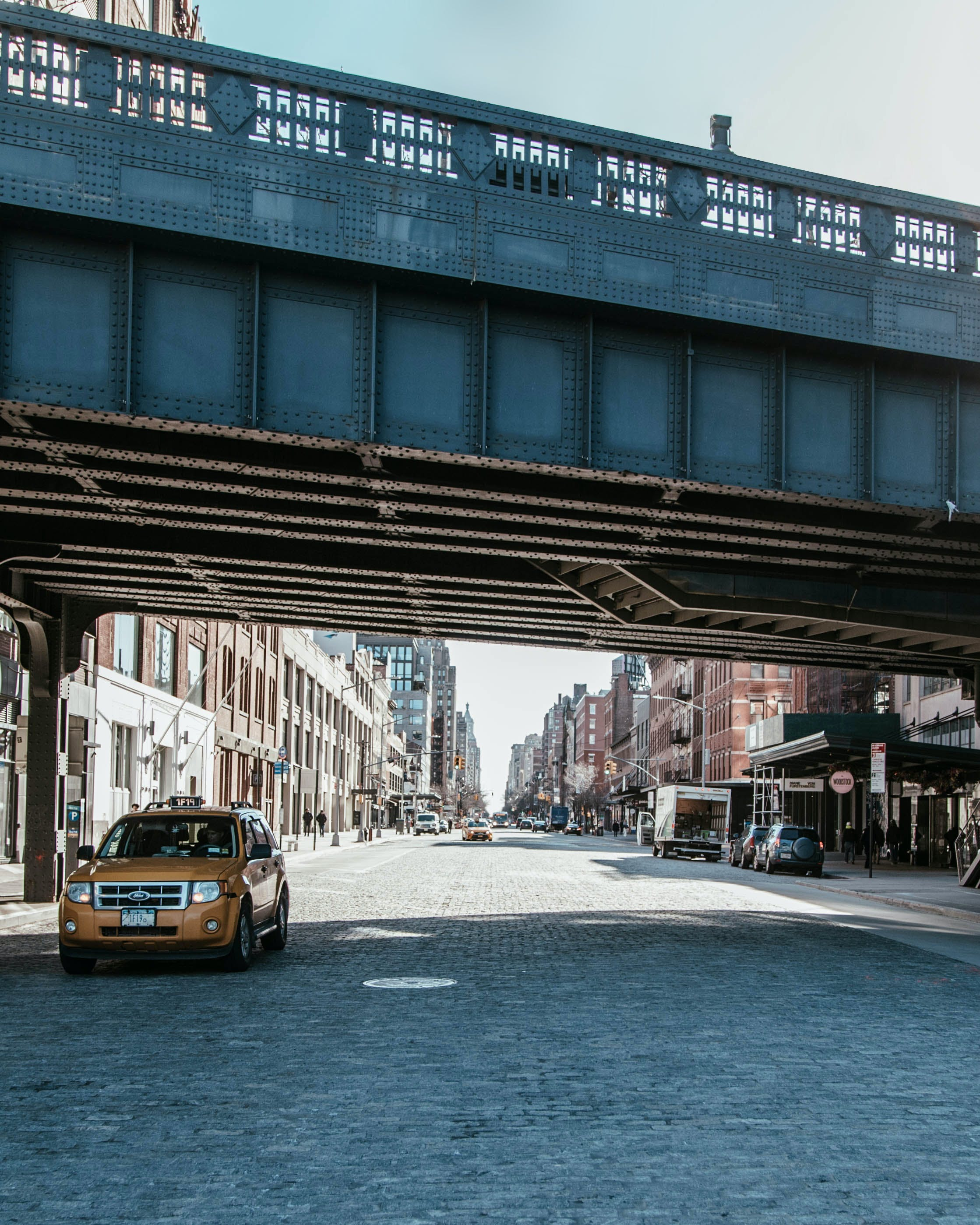 Taxi Passing Under Bridge