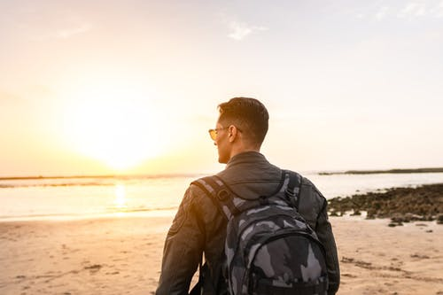Man Carrying Backpack Standing on Shore