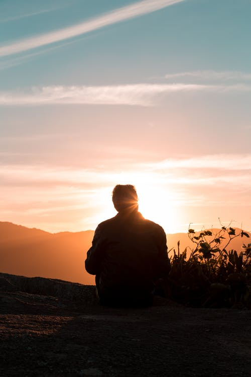 Silhouette of Person Sitting and Facing Mountain during Sunset