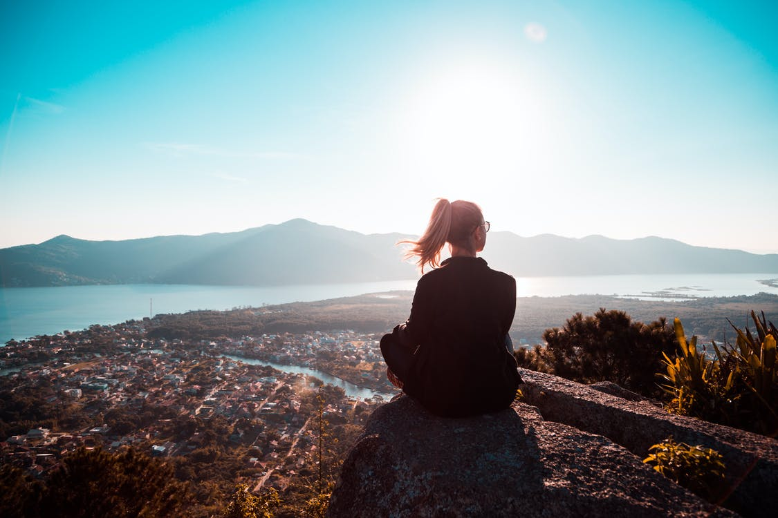Woman Sitting at the Edge of Mountain