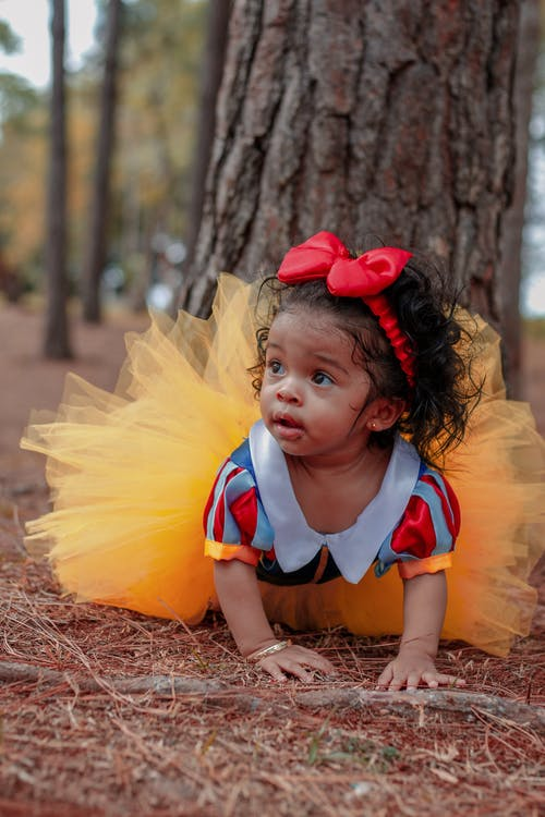 Photo of Baby Girl in Tutu Dress Crawling Near Tree