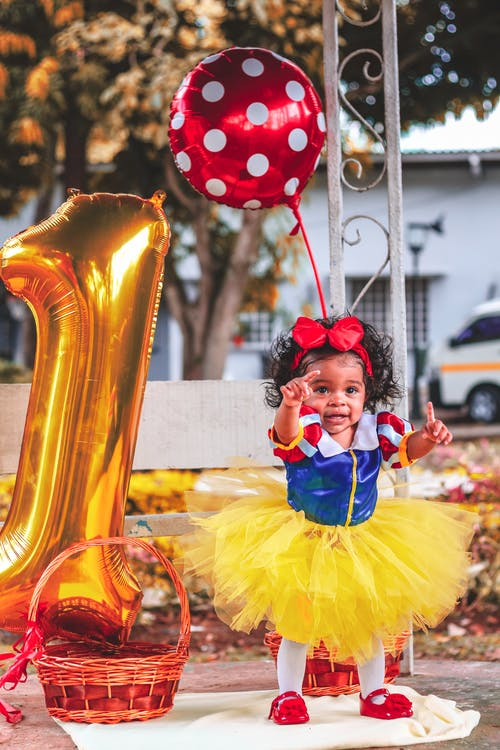 Photo of Baby Girl in Tutu Dress Standing Beside Large Gold Number 1 Balloon