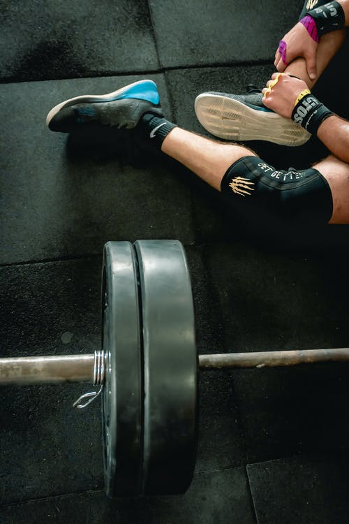 Person in Black Shoes Sitting Beside Barbell