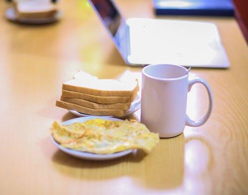 Kostnadsfri bild av bärbar dator, bordsskiva i trä, friterade ägg, hemmakontor