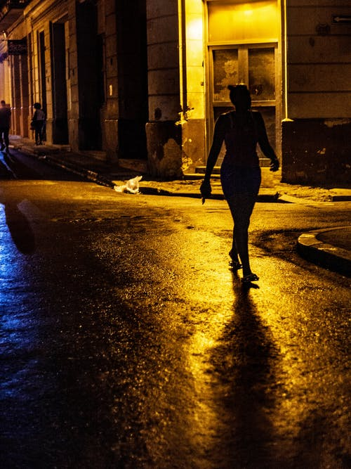 Silhouette Photo of Woman Walking on Road during Nighttime