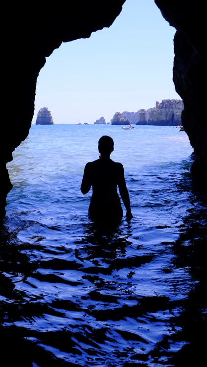 Silhouette of Woman at Blue Sea Inside Black Cave during Daytime