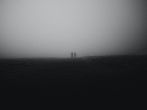 Silhouette of Two People Walking on Foggy Road