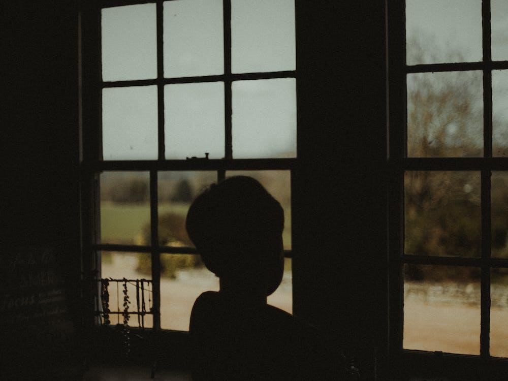 Boy Standing Near The Window