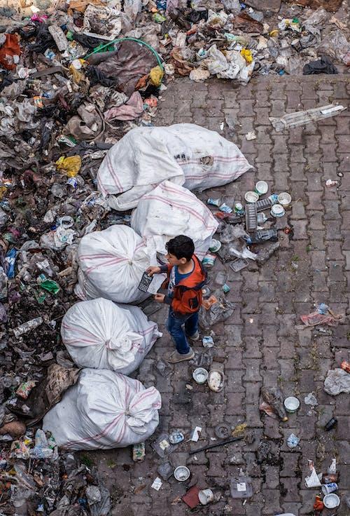 Child Standing Near Garbage