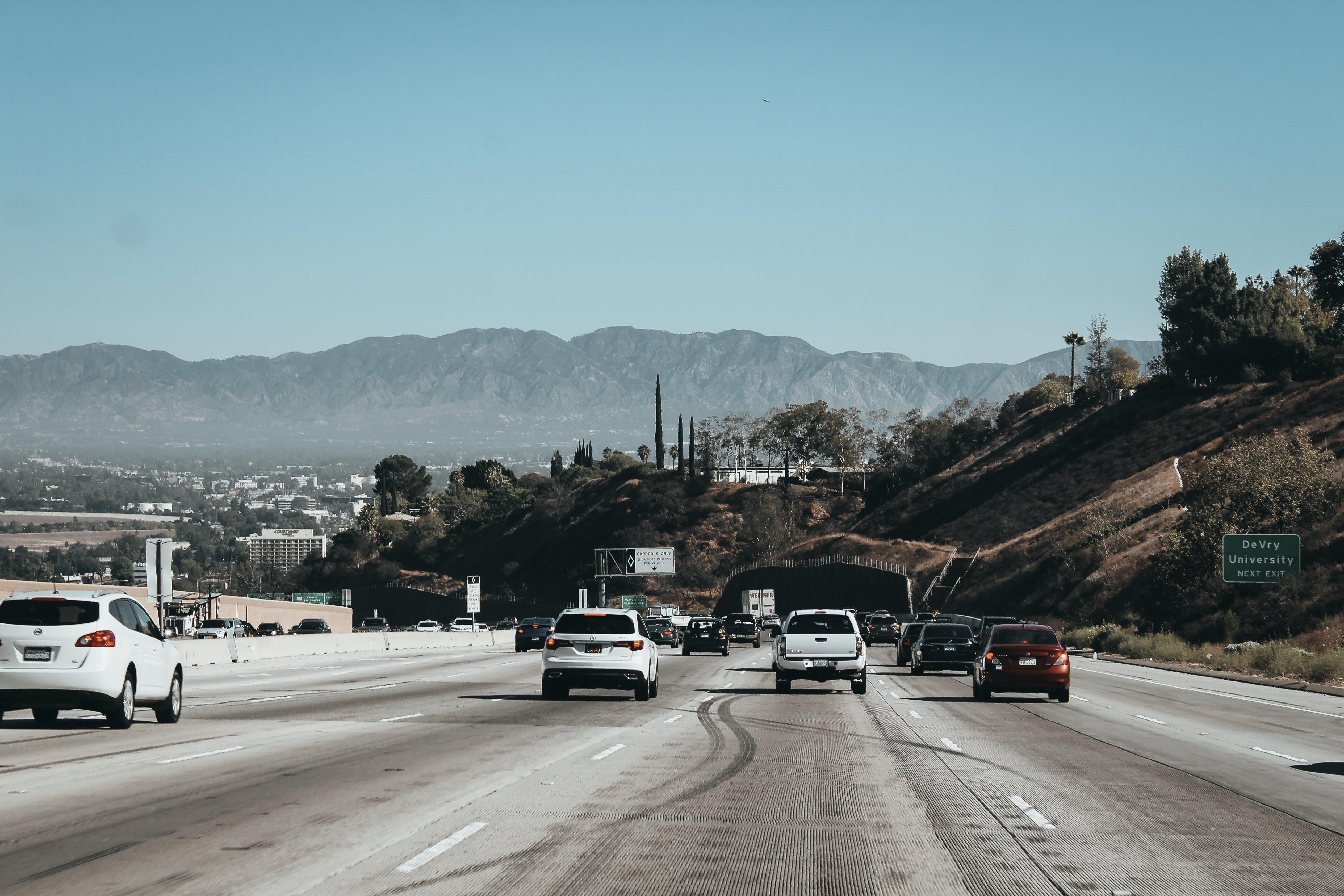 Foto d'estoc gratuïta de a l'aire lliure, arbres, asfalt, automòbils