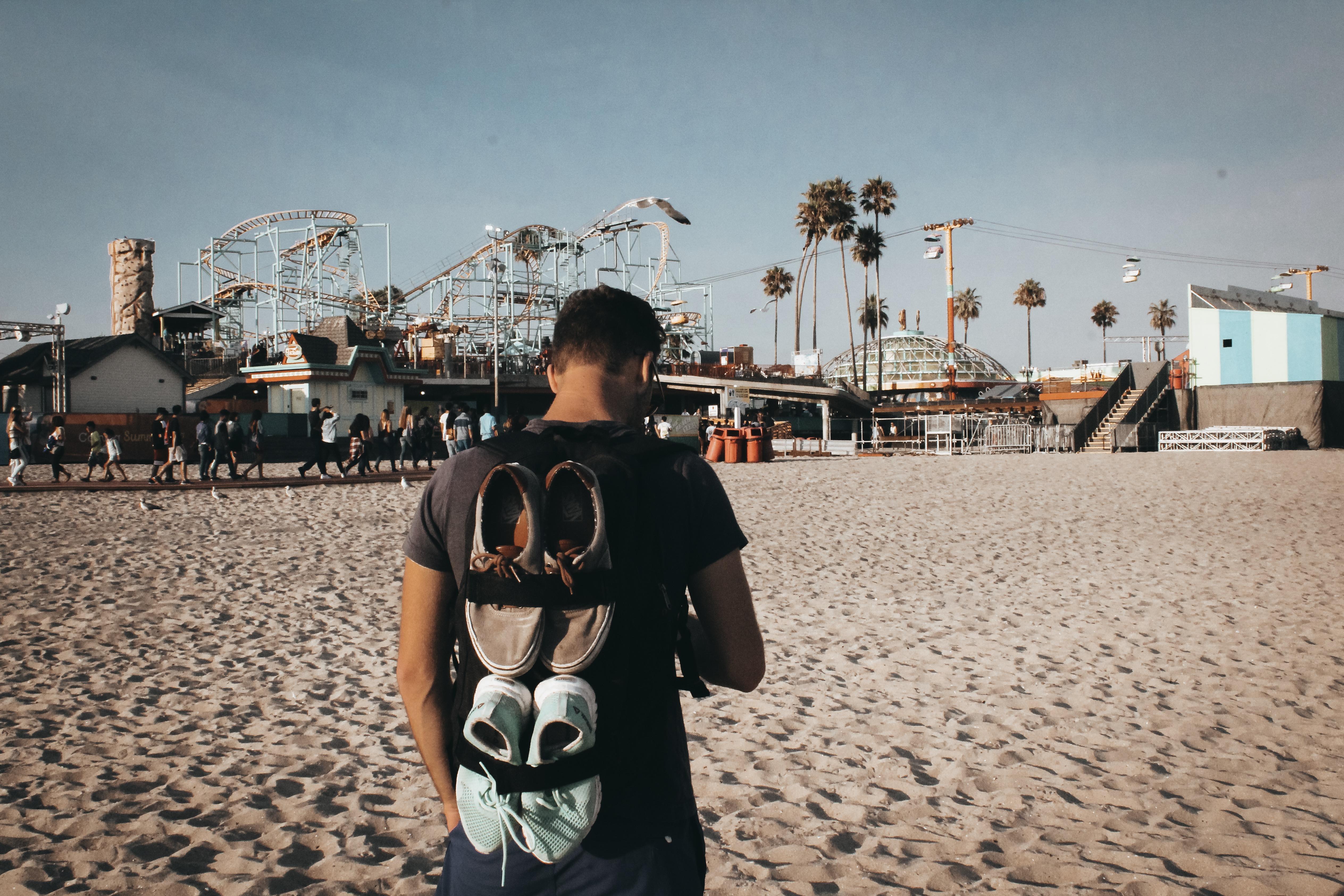 Man Standing in Beach Facing Rides