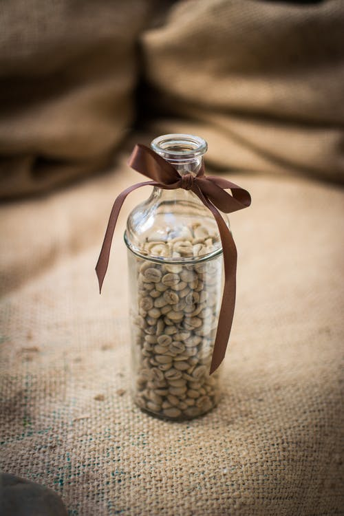 Coffee Beans in Clear Glass Bottle on Brown Textile