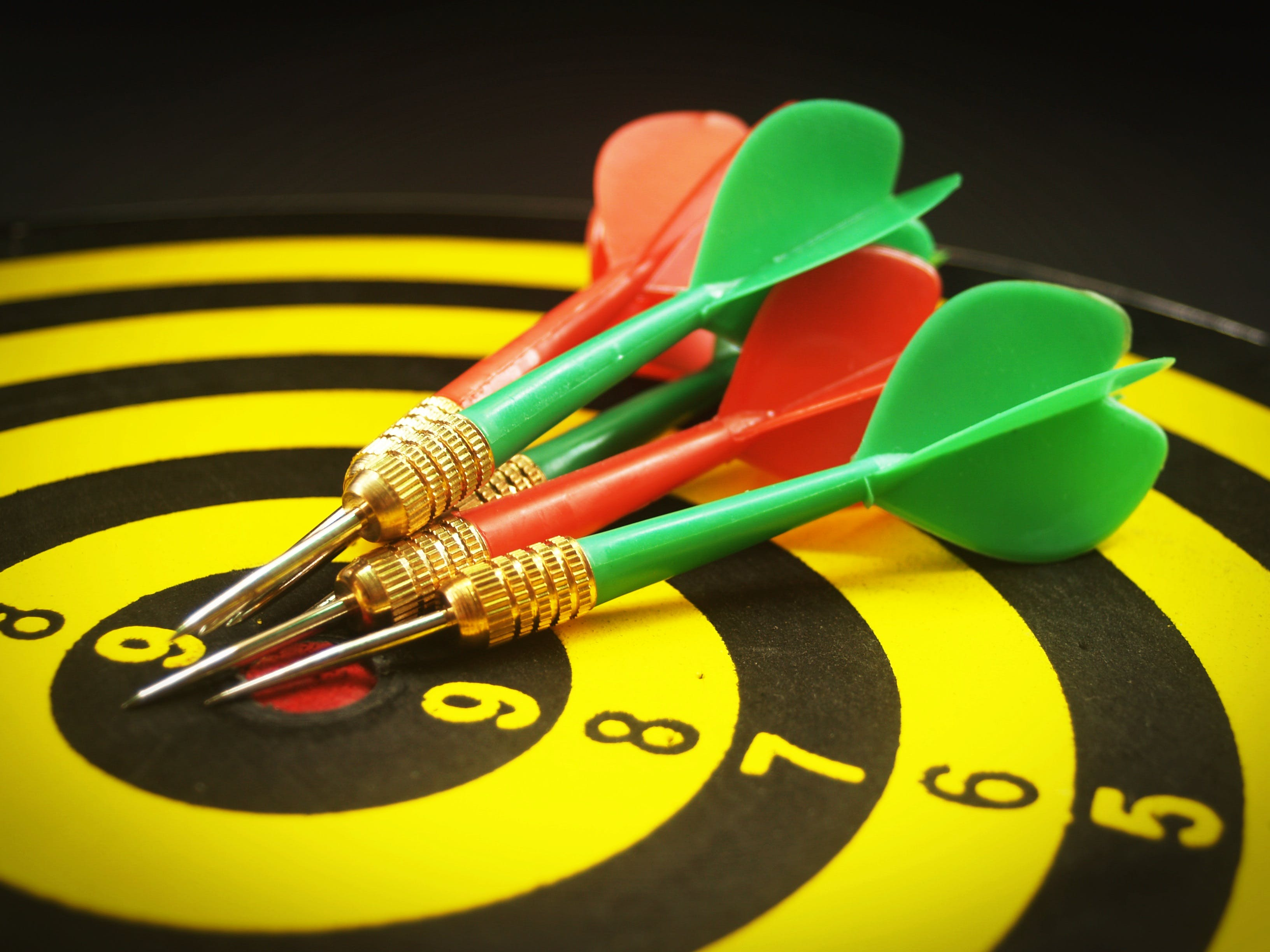 Yellow and Black Dartboard With Pins Illustration