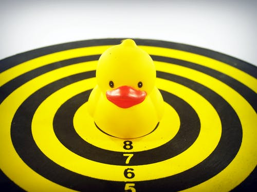 Yellow Rubber Duckie on Dart Board