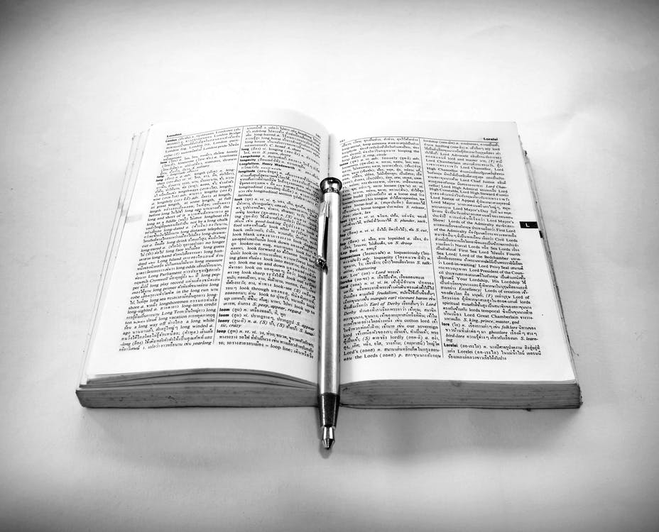 Grayscale Photography of Click Pen on Top of Opened Book