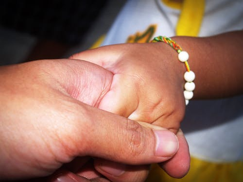 Person Holding Child's Hand