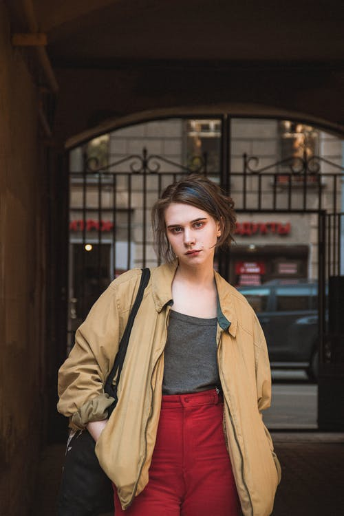 Photo of Woman in Brown Zip-up Jacket and Red Trousers Posing