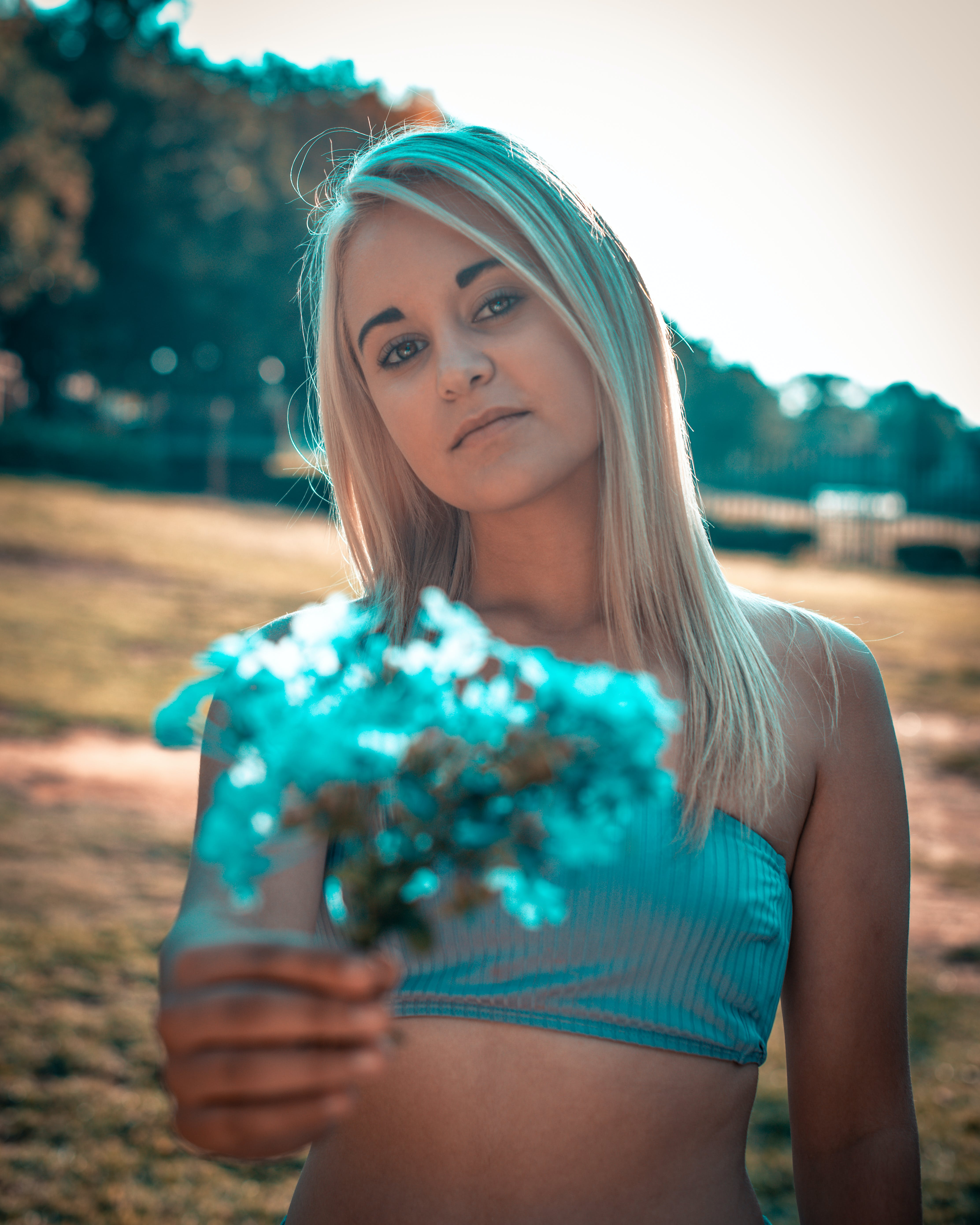 Photo of Woman in Tube Top Holding Out Blue Flowers
