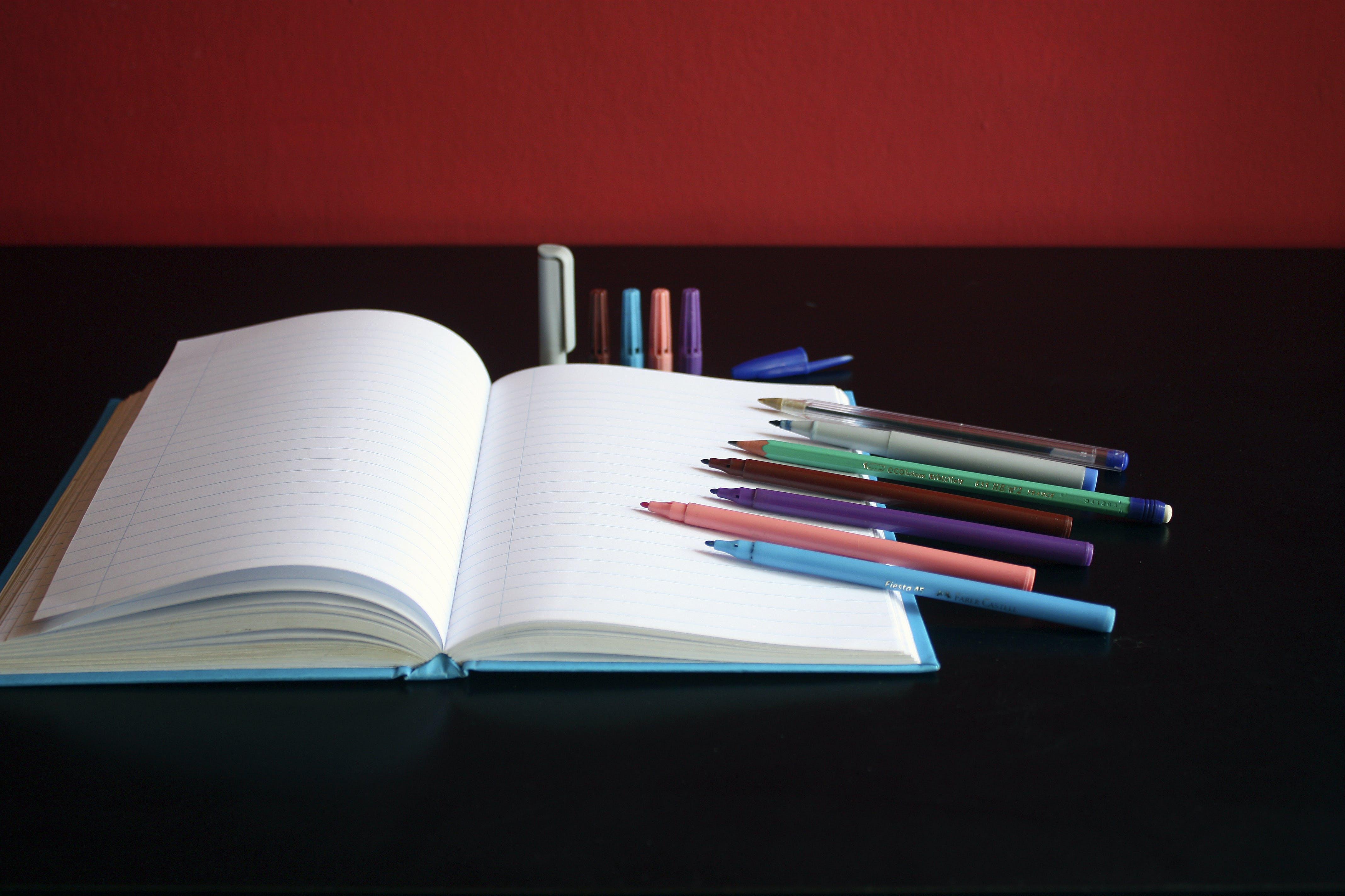 Kostenloses Stock Foto zu notizbuch, tisch, papier, markierungen