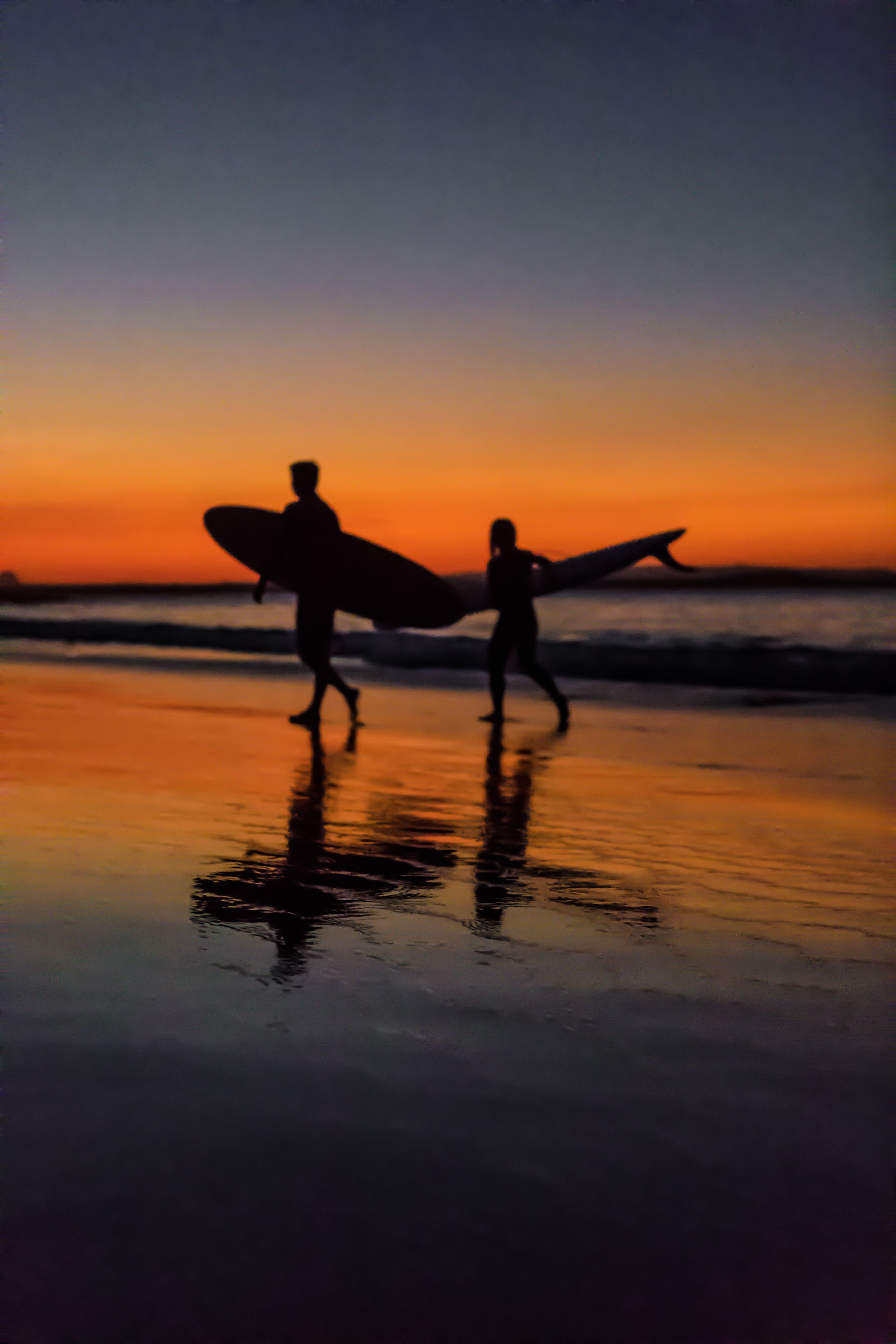 Two Surfers at the Seashore during Sunset