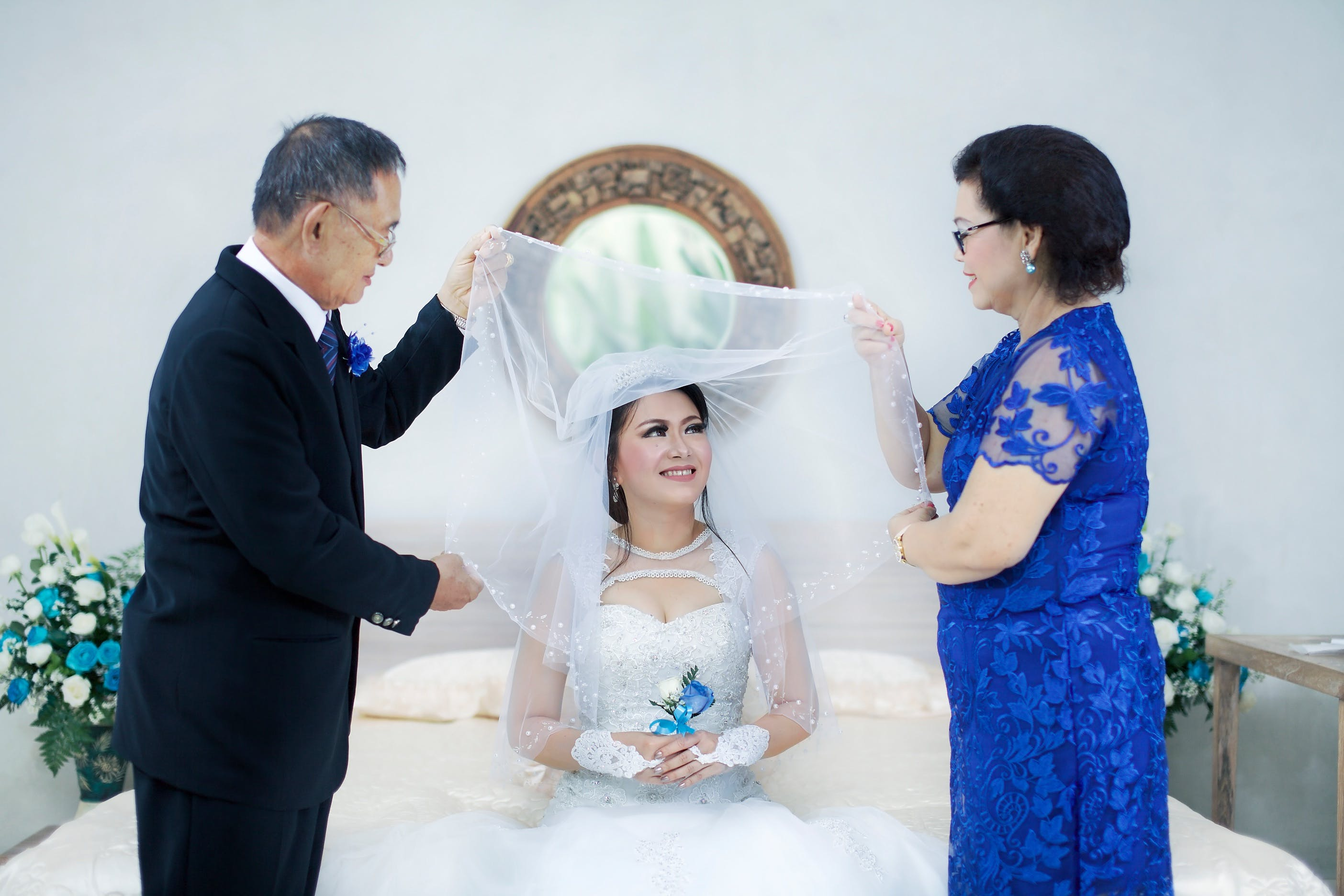 Woman in Wedding Dress Between Man in Formal Suit and Woman in Blue Dress