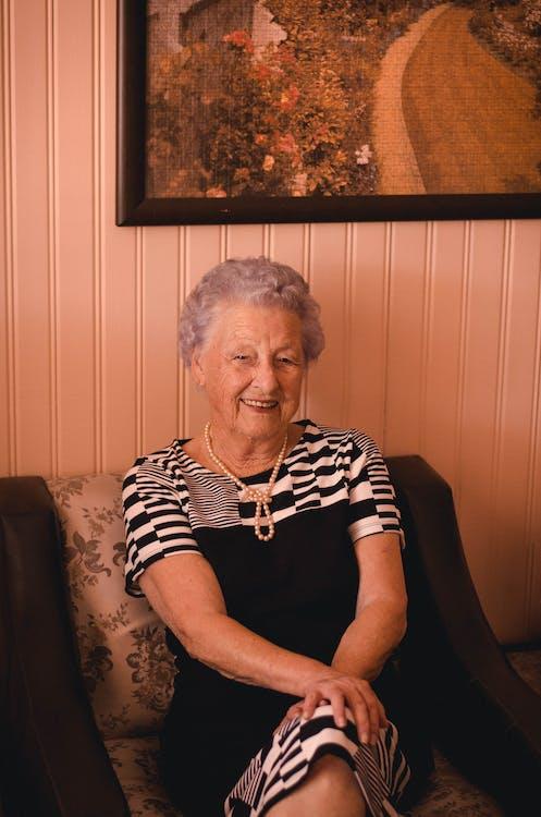 Smiling Woman Wearing Black and Grey Dress Sitting on Sofa