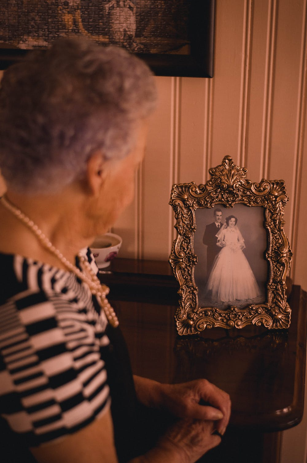 An old woman standing near the photo frame | Photo: Pexels