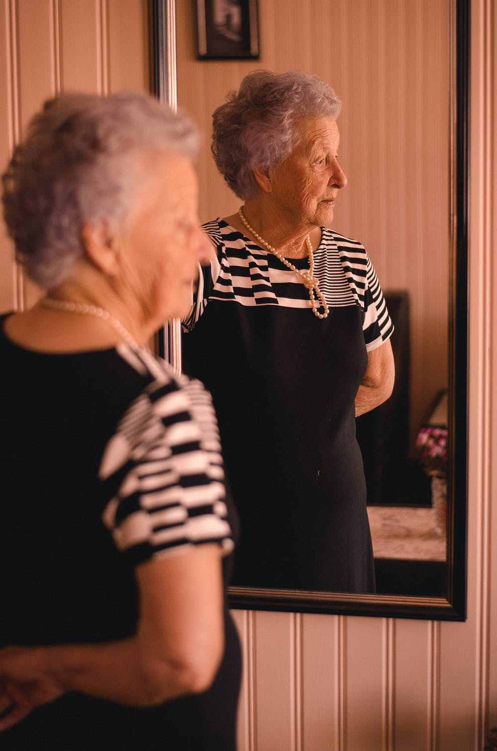 Elderly woman standing in front of a mirror. | Photo: Pexels
