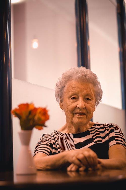 Kostnadsfri bild av äldre, ansiktsuttryck, blommor, bord