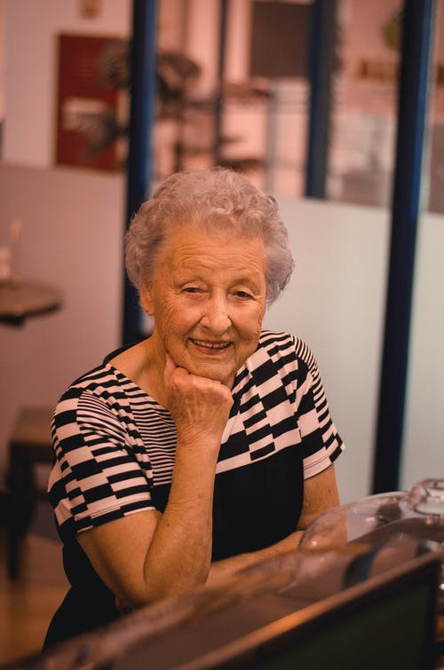 Smiling Woman Wearing Black and White Top Resting Head on Right Hand