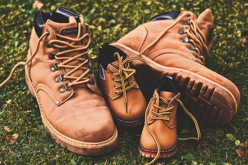 Shallow Focus Photo of Brown Work Boots on Grass