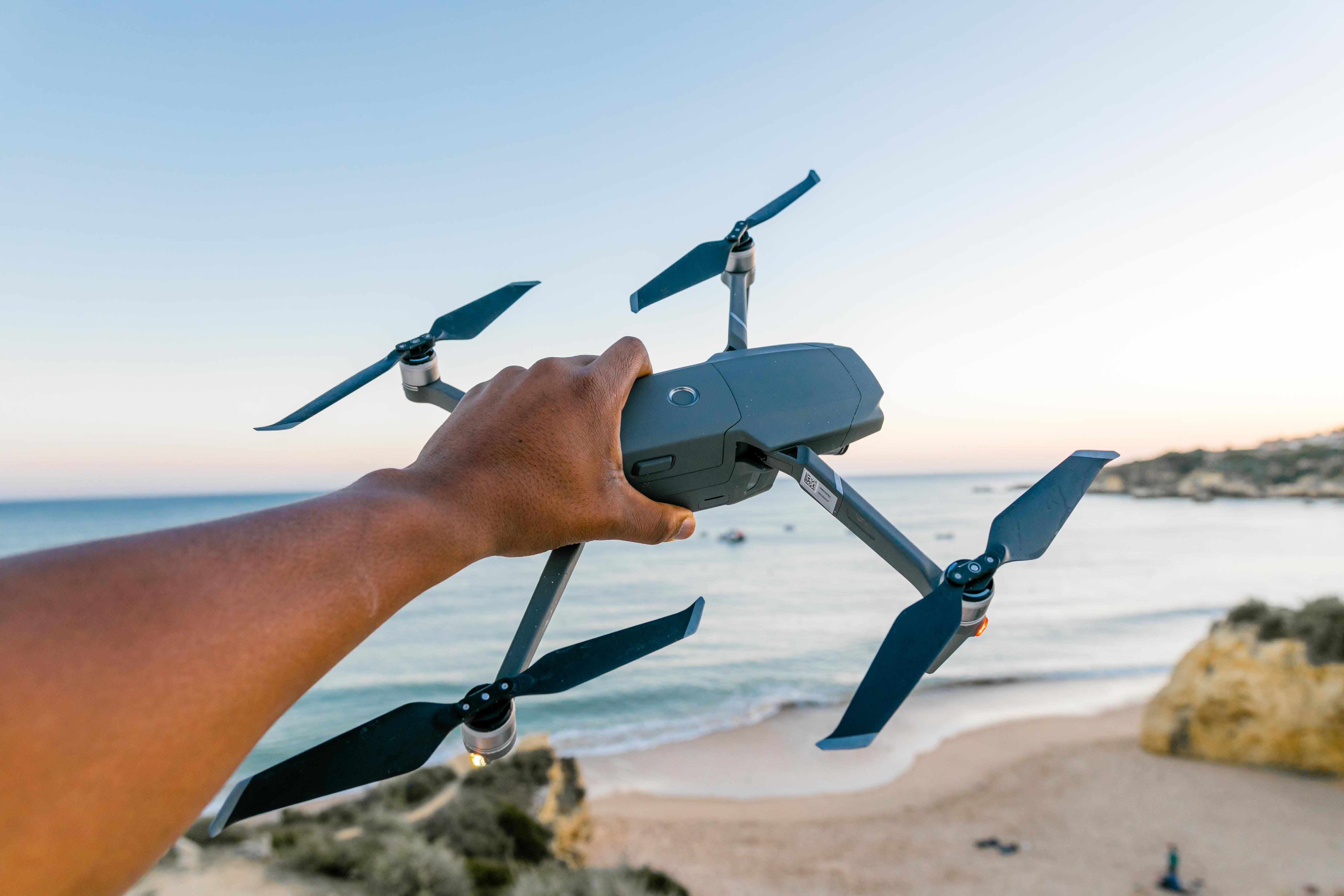 Person Holding Gray and Black Quadcopter Drone