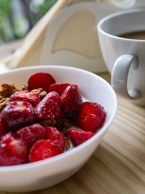 Shallow Focus Photo of Sliced Strawberries on White Ceramic Bowl