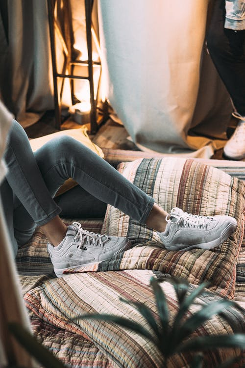 Person in White Fila Sneakers lying down in a bed