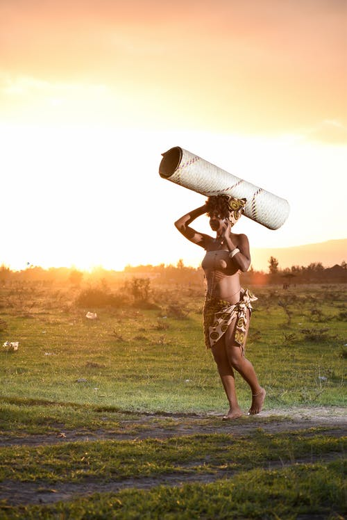 Woman Standing While Carrying White Cardboard Roll