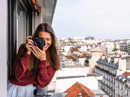 Woman Wearing Maroon Sweater Standing on Veranda Using Camera While Smiling Overlooking Houses and Buildings