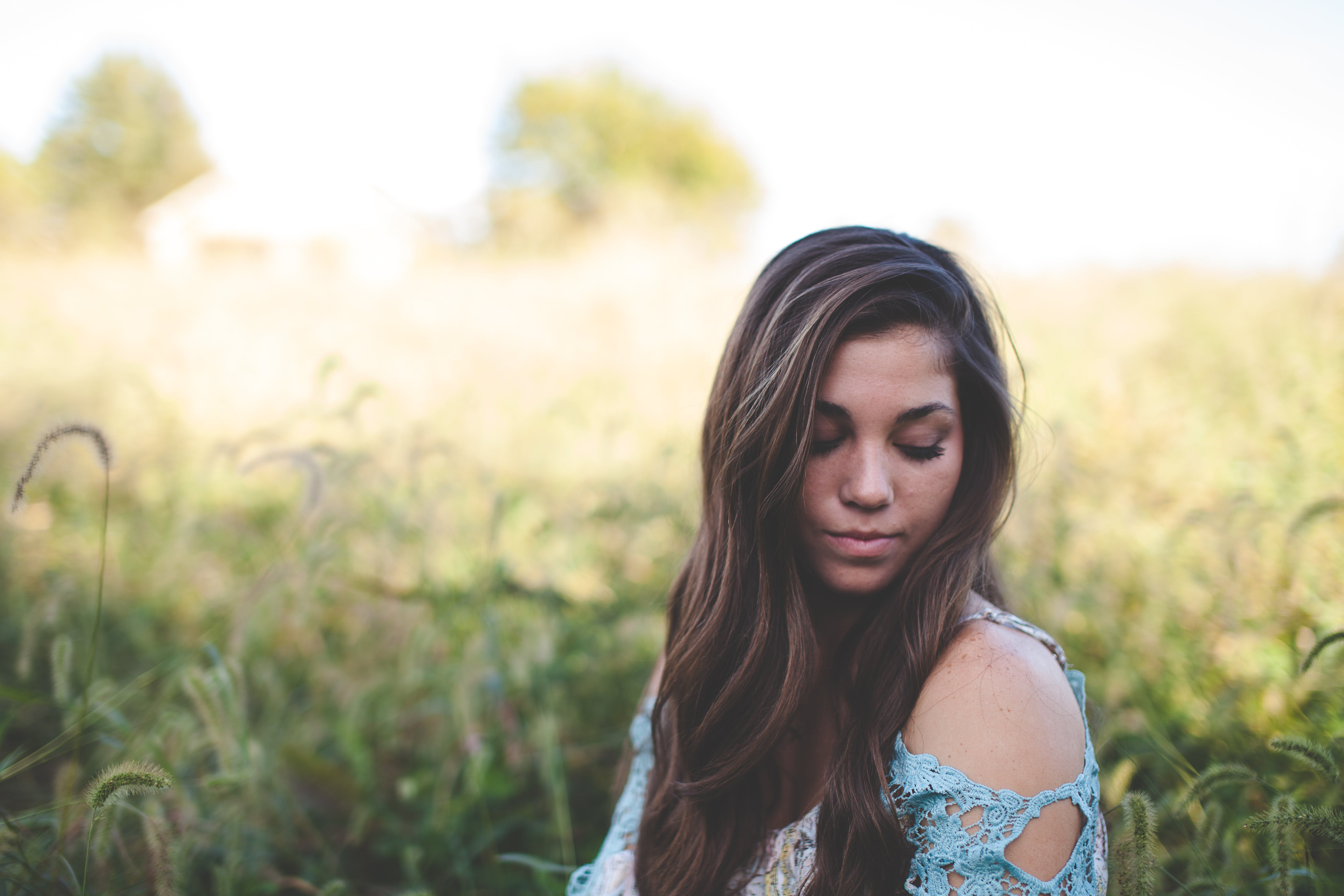Woman Wearing Teal Off Shoulder While Seating on Grass Photo